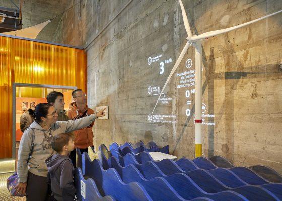 Famille pointant du doigt une éolienne dans EOL, centre d'interprétation consacré à l'éolien en mer.