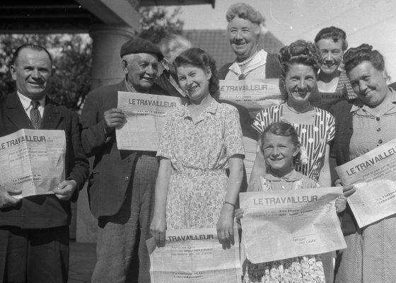Photographie d'hommes, femmes et d'une petite fille posant avec la une du journal Le Travailleur de l'Ouest à Saint-Nazaire.