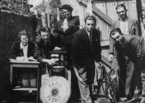 Photographie de civils de la Poche de Saint-Nazaire posant devant leur invention, le radio-pédale.
