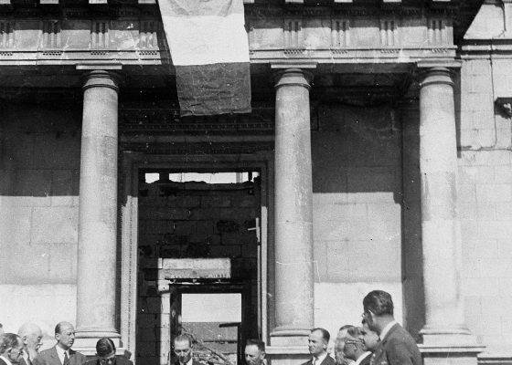 Photographie du conseil municipal de Saint-Nazaire se réunit le 9 juin 1945 devant l'ancien hôtel de ville en ruines.