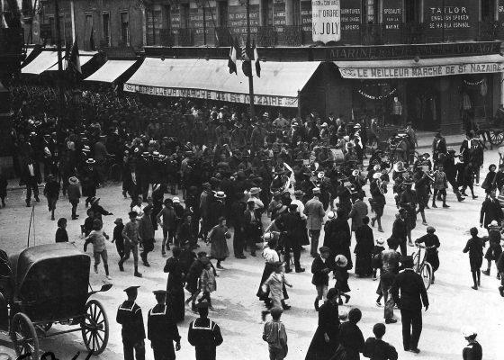 Foule composée de Nazairiens de tous âges assistant à une parade américaine au moment du débarquement à Saint-Nazaire pendant la Première Guerre mondiale.