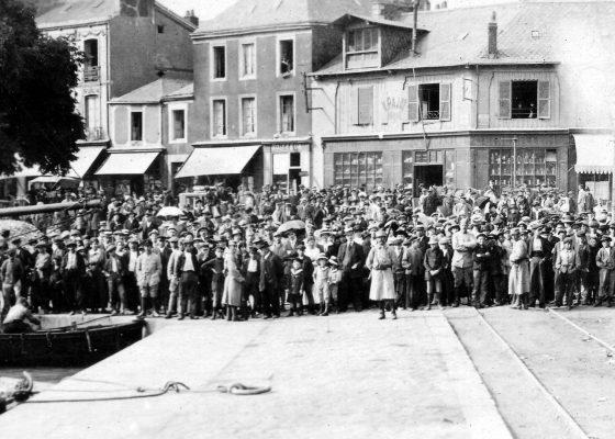 Foule de Nazairiens massée au bout d'un quai retenue par des gendarmes et assistant avec curiosité au débarquement des premiers soldats américains dans le port de Saint-Nazaire pendant la Première Guerre mondiale.