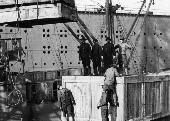 Soldats américains déchargeant d'énormes caisses en bois d'un navire avec une grue sur un quai à Saint-Nazaire pendant la Première Guerre mondiale.
