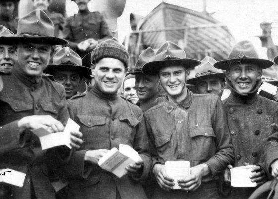 Groupe de jeunes soldats américains souriant, une boîte à tabac dans les mains devant une embarcation de sauvetage.
