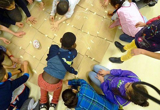 Jeunes élèves de primaire vus du dessus en train de dessiner le contour de leur main sur des cartons au cours d'une action pédagogique.