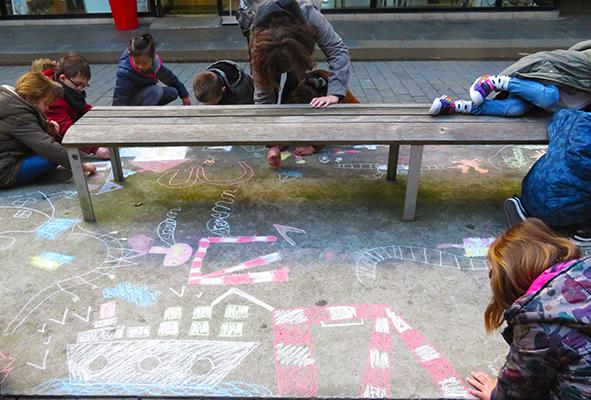 Jeunes élèves de primaire dessinant à la craie sur le sol dans la ville près du centre commercial le Paquebot.