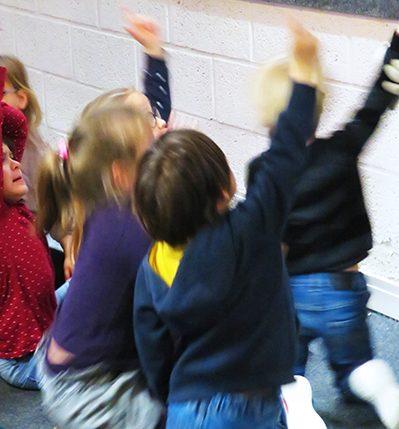 Jeunes élèves assis de dos en train de lever le doigt pendant une action pédagogique dans l'Écomusée.