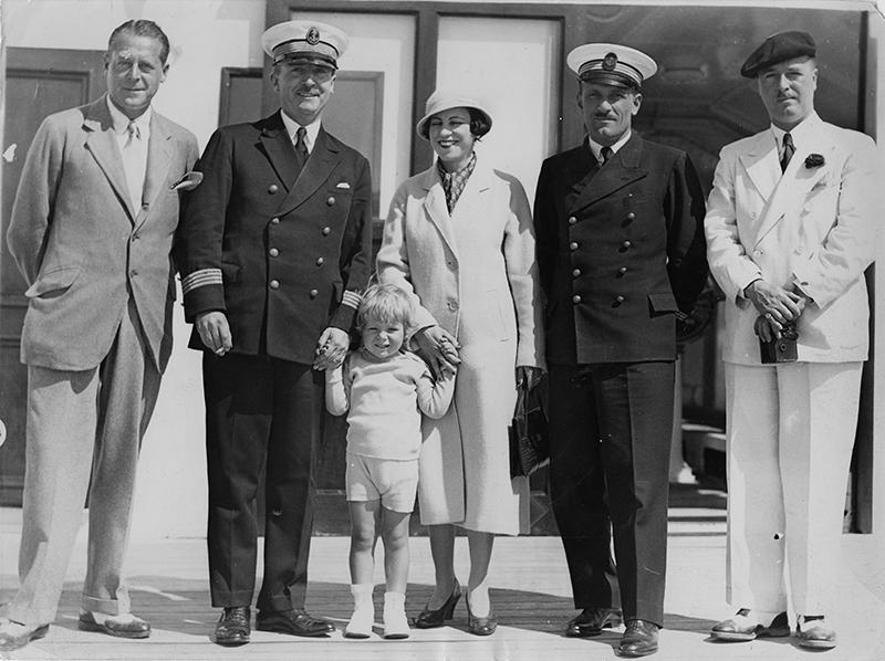 Deux hommes, une femme et un enfant posent avec le capitaine et un officier sur le pont du paquebot Ile-de-France, le 28 juillet 1933.