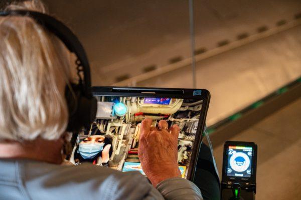 Femme assise dans un fauteuil roulant de dos avec une tablette numérique dans les mains.