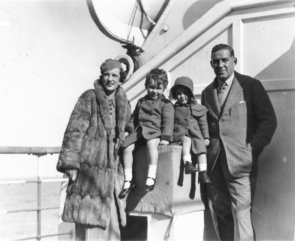 Un couple pose avec ses deux jeunes enfants sur le pont des embarcations du paquebot Ile-de-France, le 25 octobre 1933.