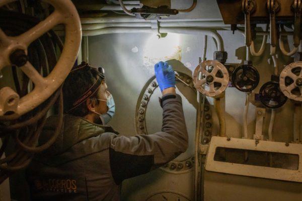 Un homme, équipé d'une lampe frontale et d'une combinaison, applique un produit au coton-tige sur une surface intérieure abîmée du sous-marin Espadon