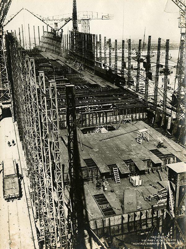 Vue aérienne d'ouvriers procédant au montage des barreaux et membrures ainsi qu'à l'assemblage des ponts du paquebot Ile-de-France.