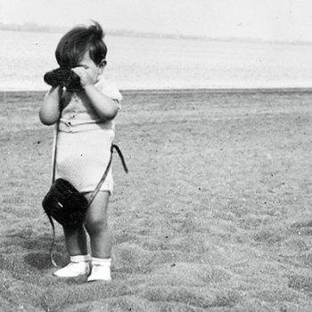 Petit garçon regardant à travers des jumelles sur une plage.