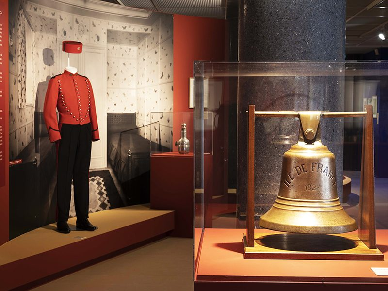 """Vue d'une cloche et d'un costume de groom dans l'exposition """"L'Art déco, un art de vivre : le paquebot Ile-de-France"""" au musée des Années 30 de Boulogne-Billancourt."""