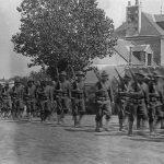 Colonne de soldats américains longeant une maison dans la campagne nazairienne.