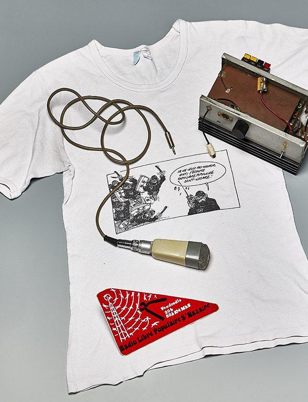 Tee-shirt blanc sur lequel sont posés un émetteur radio, un micro et un autocollant de la Radio Libre Populaire de Saint-Nazaire.
