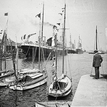 À droite de l'image, un homme regarde des paquebots dans le bassin de Saint-Nazaire.