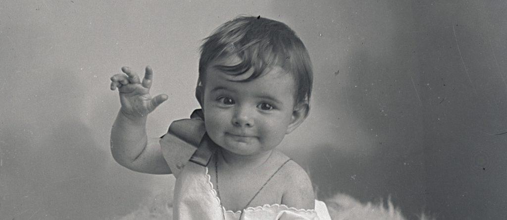 Portrait d'un bébé faisant un geste de la main en direction de l'objectif dans un studio du début du 19ème siècle.
