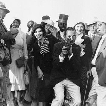 Des passagers posent dans une vedette d'embarquement autour d'un photographe qui fait face à l'objectif.
