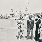Quatre femmes et un homme posant devant le bassin du port de Saint-Nazaire et un navire militaire.