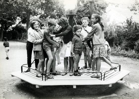 Des enfants jouent sur un tourniquet dans un parc en juillet 1963.