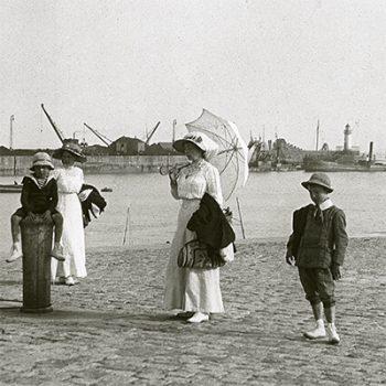 Deux femmes en robes blanches du début du siècle posent avec deux enfants au niveau de l'avant-port de Saint-Nazaire.