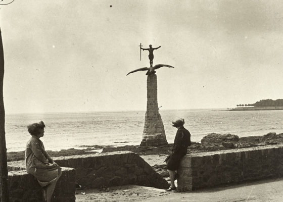 Deux femmes assises sur un muret sur le front de mer regarde le monument américain dressé à la suite de la Première Guerre mondiale dans les années 1930.