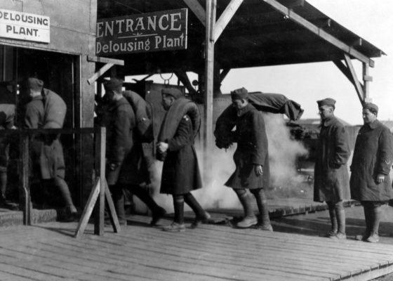 Soldats américains faisant la queue avec leur paquetage devant le bâtiment d'épouillage à Saint-Nazaire à la fin de la guerre.
