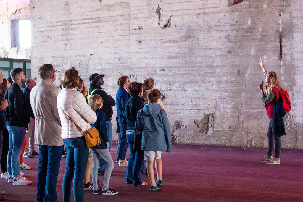Guide s'adressant à un groupe lors d'une visite de la base sous-marine pendant les Journées du patrimoine, événement de la Saison patrimoine.