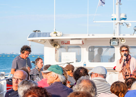 """Visiteurs sur le pont d'un navire lors de la croisière apéritive musicale """"Accords maritimes"""", événement de la Saison patrimoine 2019."""