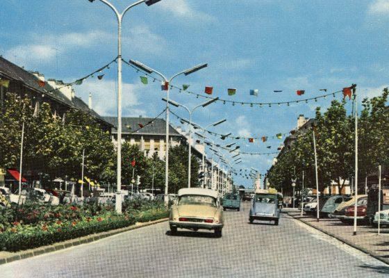 Voitures des années 1950 roulant sur l'avenue de la République pavoisée à Saint-Nazaire.