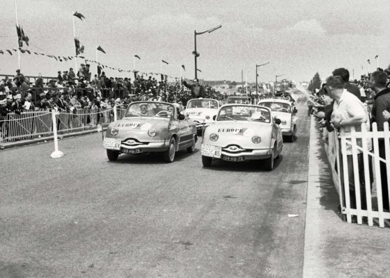 Voitures Panhard paradant devant la foule lors du passage du Tour de France cycliste en 1958.