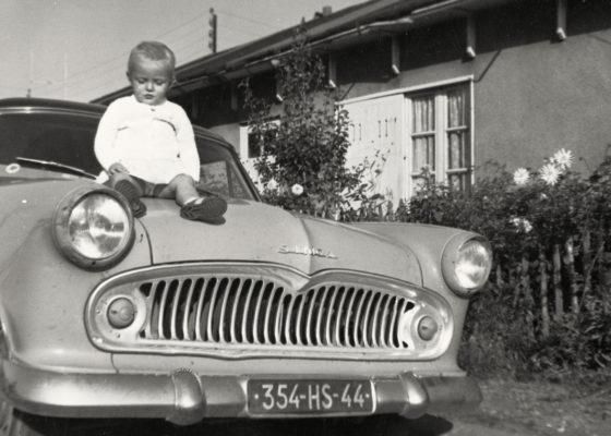 Jeune enfant assis sur le capot d'une voiture de marque Simca devant un baraquement provisoire dans les années 1950.