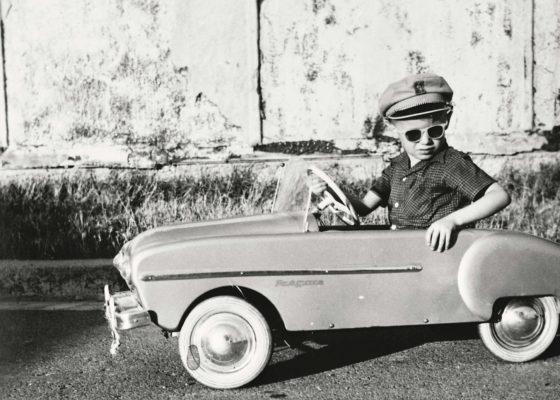 Enfant au volant d'une voiture-jouet Renault Frégate.