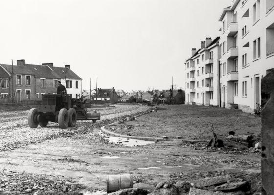 Ouvrier sur un tracteur procédant aux travaux de voirie devant les HLM de Cardurand à Saint-Nazaire dans les années 1950.