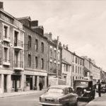 Photographie en noir et blanc de voitures des années 1950 garées dans une rue de Saint-Nazaire dont deux cafés à identifier.