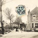Carte postale timbrée du début du 20e siècle représentant une grande bâtisse carrée en pierre devant une route, sur celle-ci des piétons et des cyclistes.