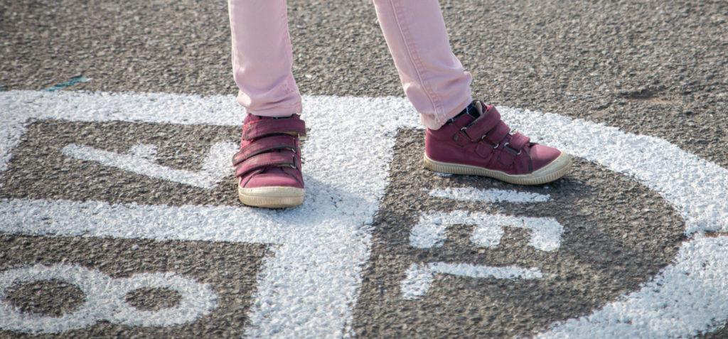 Gros plan sur les jambes d'une enfant qui joue à la marelle.