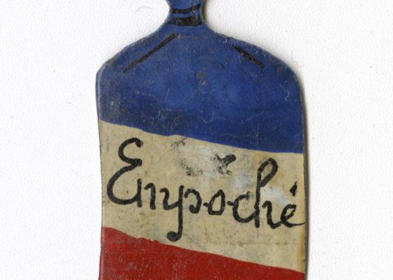 """Insigne en forme de petit sac arborant les couleurs du drapeau français, au centre le mot """"empoché"""" en référence à la Poche de Saint-Nazaire."""
