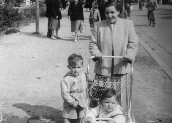 Photographie en noir et blanc représentant une femme avec deux enfants dont un en poussette, à l'arrière-plan des gens marchent dans la rue.