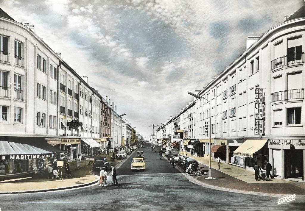 Carte postale colorisée montrant la perspective de l'avenue de la République avec les immeubles la bordant de chaque côté.