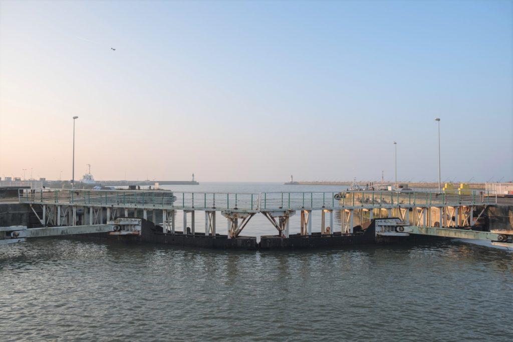 Vue panoramique sur les portes d'une écluse, en arrière-plan l'avant-port de Saint-Nazaire et l'océan.