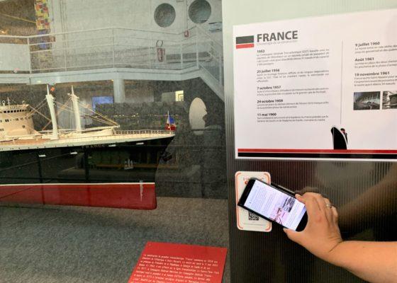 Main tenant un smartphone devant un QR code à côté d'une maquette du paquebot France (1962) à l'Écomusée.