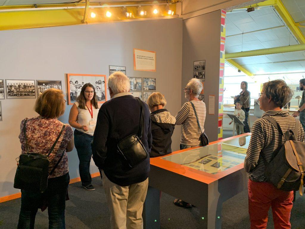 Groupe de visiteurs devant une médiatrice dans la salle d'exposition de l'Écomusée