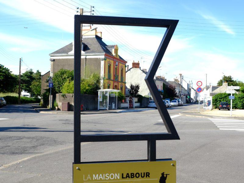 """Vue de la façade colorée d'une maison à travers un mobilier urbain du parcours """"Méan-Penhoët, récits de quartier""""."""