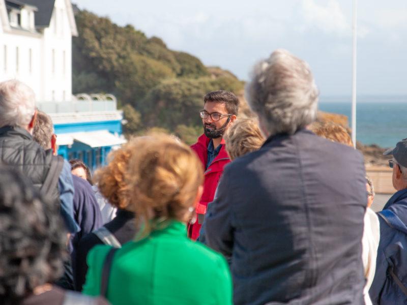 Guide s'adressant à un groupe de visiteurs lors d'une visite guidée devant l'hôtel de la plage à Saint-Marc-sur-Mer.