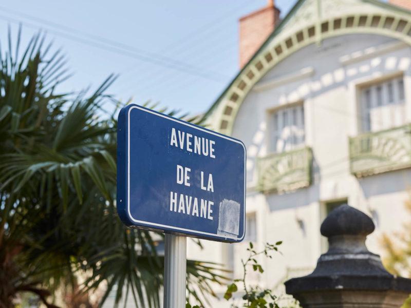 Panneau de rue indiquant l'avenue de la Havane devant la façade d'une maison bourgoise.