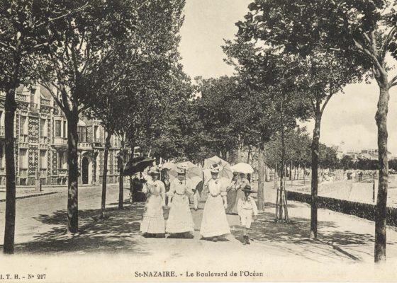 Trois femmes en robe de dentelle blanche et ombrelle se baladent face à nous sur le front de mer vers 1910.