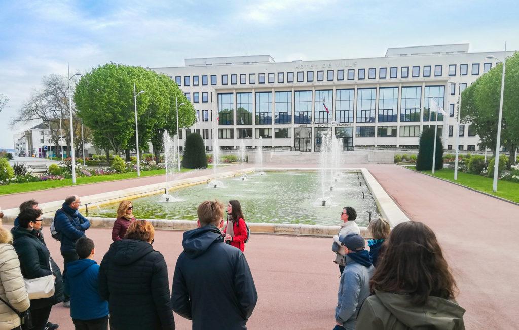 Groupe de personnes suivant une visite face au bassin de l'hôtel de ville à Saint-Nazaire.