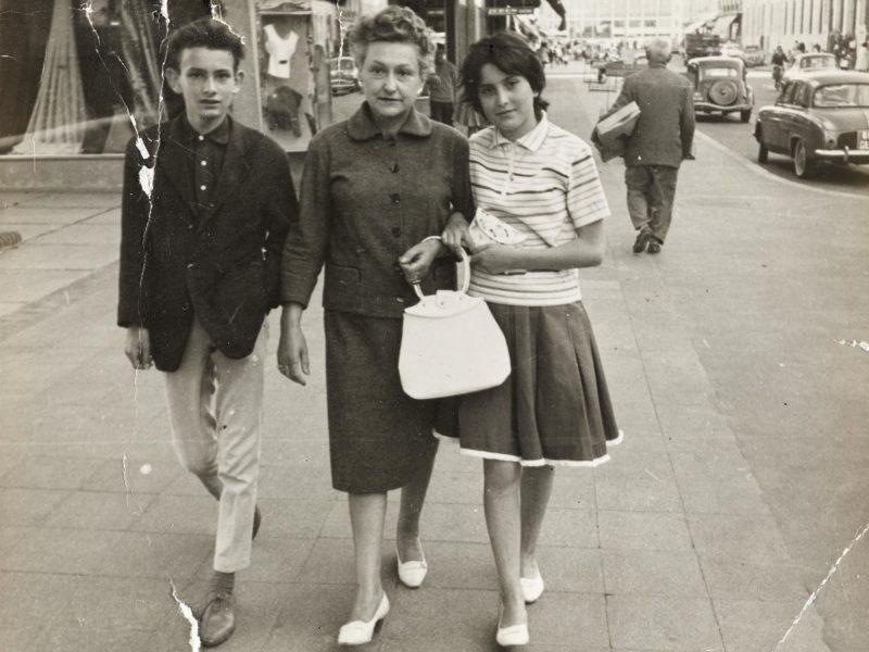 Photographie en noir et blanc d'une femme entourée de deux adolescents marchant dans l'avenue de la République à Saint-Nazaire dans les années 1960.
